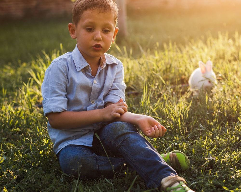 a young boy sitting on top of a grass covered field